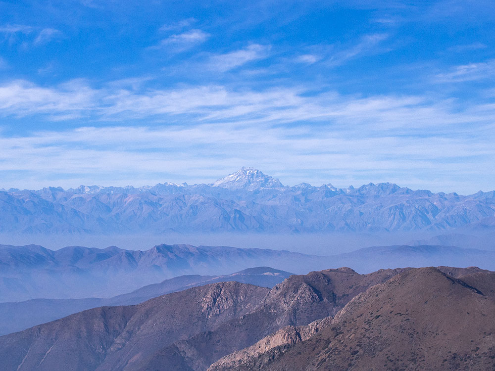 From top of the Coastal Range we can observe the Central Valley with a few hills and the Andes with Mount Aconcagua in the background.